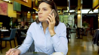 Businesswoman eating lunch and receiving bad news, steadycam shot
