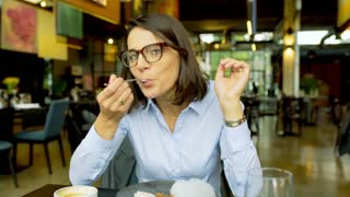 Businesswoman eating lunch and showing thumbs to the camera, steadycam shot