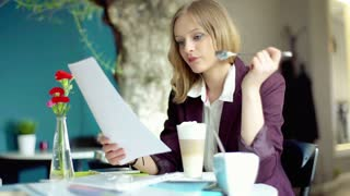 Businesswoman eating mousse from the coffee and reading papers
