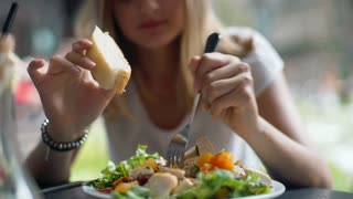 Businesswoman eating salad and bread for lunch in the outdoor cafe
