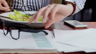 Businesswoman eating salad and working on documents, steadycam shot