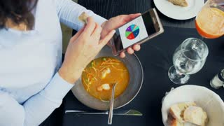 Businesswoman eating soup and working on smartphone, steadycam shot