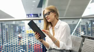Businesswoman having painful headache while using tablet on the train station