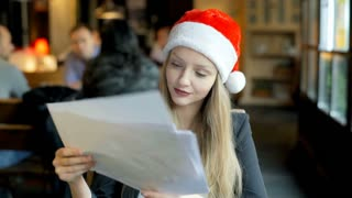 Businesswoman in Santa's hat reading papers and smiling to the camera, steadycam