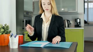 Businesswoman reading documents and drinking coffee in the apartment, steadycam