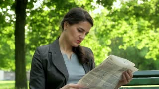 Businesswoman reading newspaper in the park
