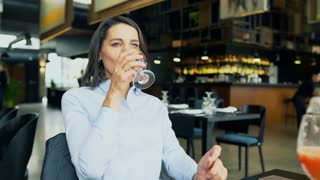 Businesswoman relaxing and drinking water in the cafe, steadycam shot