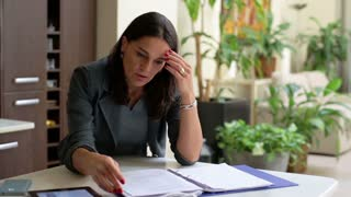 Businesswoman sitting in office wrong results in documents, steadycam shot.