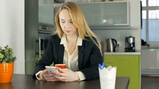 Businesswoman sitting in the apartment and texting on smartphone, steadycam shot