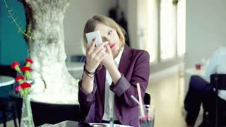 Businesswoman sitting in the cafe and powder her face, steadycam shot