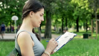 Businesswoman sitting in the park and looking for a job