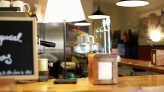 Businesswoman smiling to camera and drinking coffee in cafe, steadycam shot.