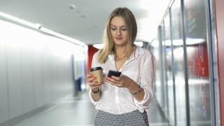 Businesswoman smiling to the camera while drinking coffee and using smartphone i