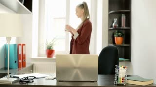 Businesswoman standing next to the window with cup of coffee, steadycam shot