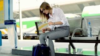 Businesswoman taking her smartphone from suitcase on platform, steadycam shot