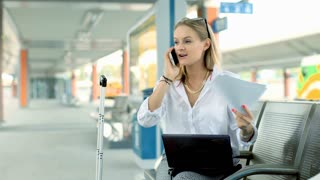 Businesswoman talking on cellphone and checking documents on the train station