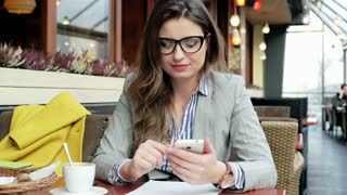 Businesswoman texting on smartphone and smiling to the camera