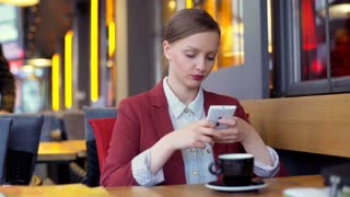 Businesswoman texting on smartphone in the cafe and drinking coffee