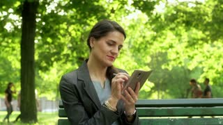 Businesswoman using smartphone and smiling to the camera