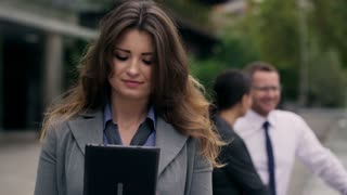Businesswoman using tablet and smiling to the camera on public square