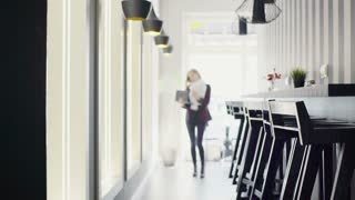 Businesswoman walking in the cafe and have a lot in her plate