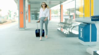 Businesswoman walking with suitcase and looking for her train, steadycam shot