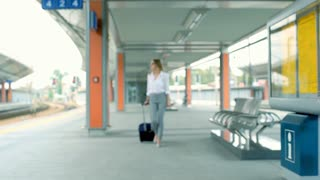 Businesswoman walking with suitcase and smiling to the camera, steadycam shot