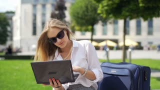 Businesswoman working on laptop and drinking coffee outdoors