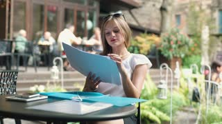 Businesswoman working on papers in the outdoor cafe and smiling to the camera