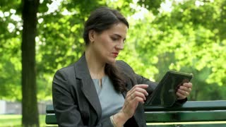 Businesswoman working on tablet in the park