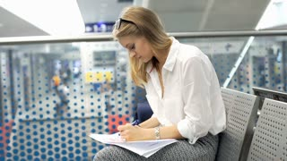 Businesswoman writing something and doing serious look to the camera