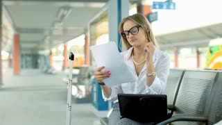 Businesswoman writing something on documents while sitting on the train station