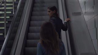 Businesswomen riding by escalator, slow motion shot at 240fps, steadycam shot