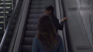 Businesswomen riding by escalator, slow motion shot, steadycam shot