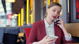 Busy businesswoman having two business calls in the cafe