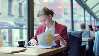 Busy businesswoman looking on graphs and writing something