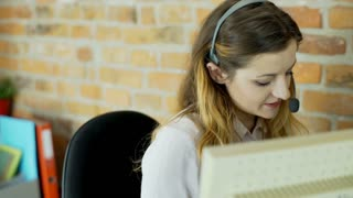 Call center agent looks happy while talking with customer