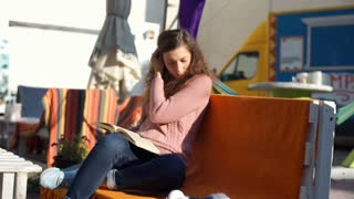 Calm girl sitting outdoors and reading interesting book