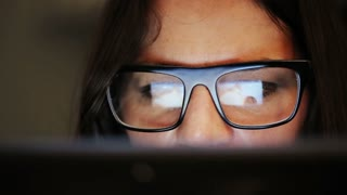 Closeup shot of woman in glasses surfing internet at night