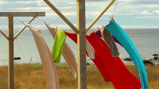 Colourful towels waving on wind by seashore, slow motion shot at 240 fps
