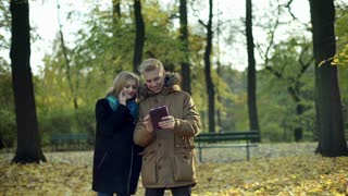 Couple browsing internet on tablet in the autumnal park