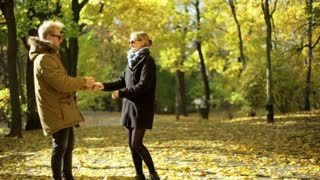 Couple dancing in the autumnal park and smiling to the camera