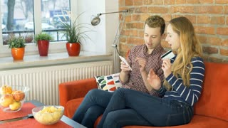 Couple doing online shopping while sitting in the flat, steadycam shot