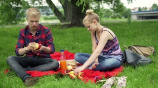 Couple eating fruits and talking on the picnic