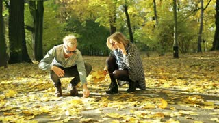 Couple gathering maple leaves and smiling to the camera in the park