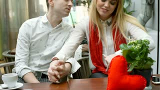 Couple holding each other hands while sitting in the cafe and smiling to the cam