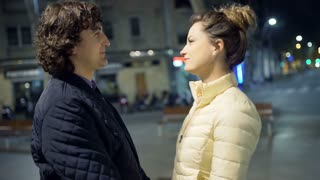 Couple holding hands while standing in the city at night, steadycam shot