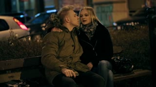 Couple kissing and talking on the bench at night