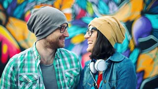 Couple looking and smiling to each other while standing next to the graffiti