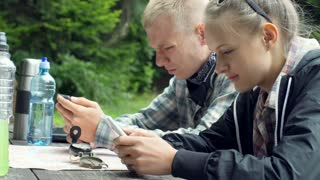 Couple looking very absorbed while using modern technologies
